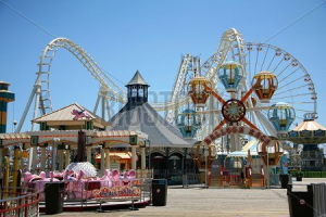 Roller coaster, ferris wheel, and carousel at a midway