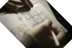 Close-up of hands working on sudoku