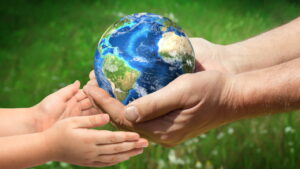 Adult hands holding a globe passing it to a child's hands