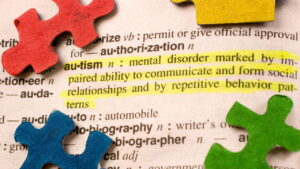 "Puzzle pieces on sitting on dictionary open to ""Autism"" definition"