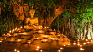 Buddha sitting by tree with candles around