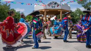 Colourful mexican men and women in traditional dress dancing