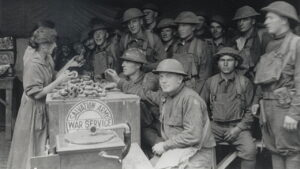 Salvation Army member handing doughnuts to World War 1 soldiers