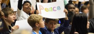 "Children from different cultures, one holding a ""Peace"" sign"