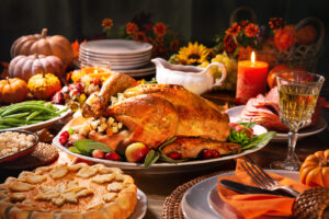 Roast turkey, pumpkin pie, beans, potatoes, gravy, folded orange napkin with fork and knife, lit candle, whole squashes
