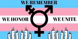 "Blue, pink and white stripes with ""we remember"", ""we honor"", ""we unite"", and symbols for women, men, and trans"